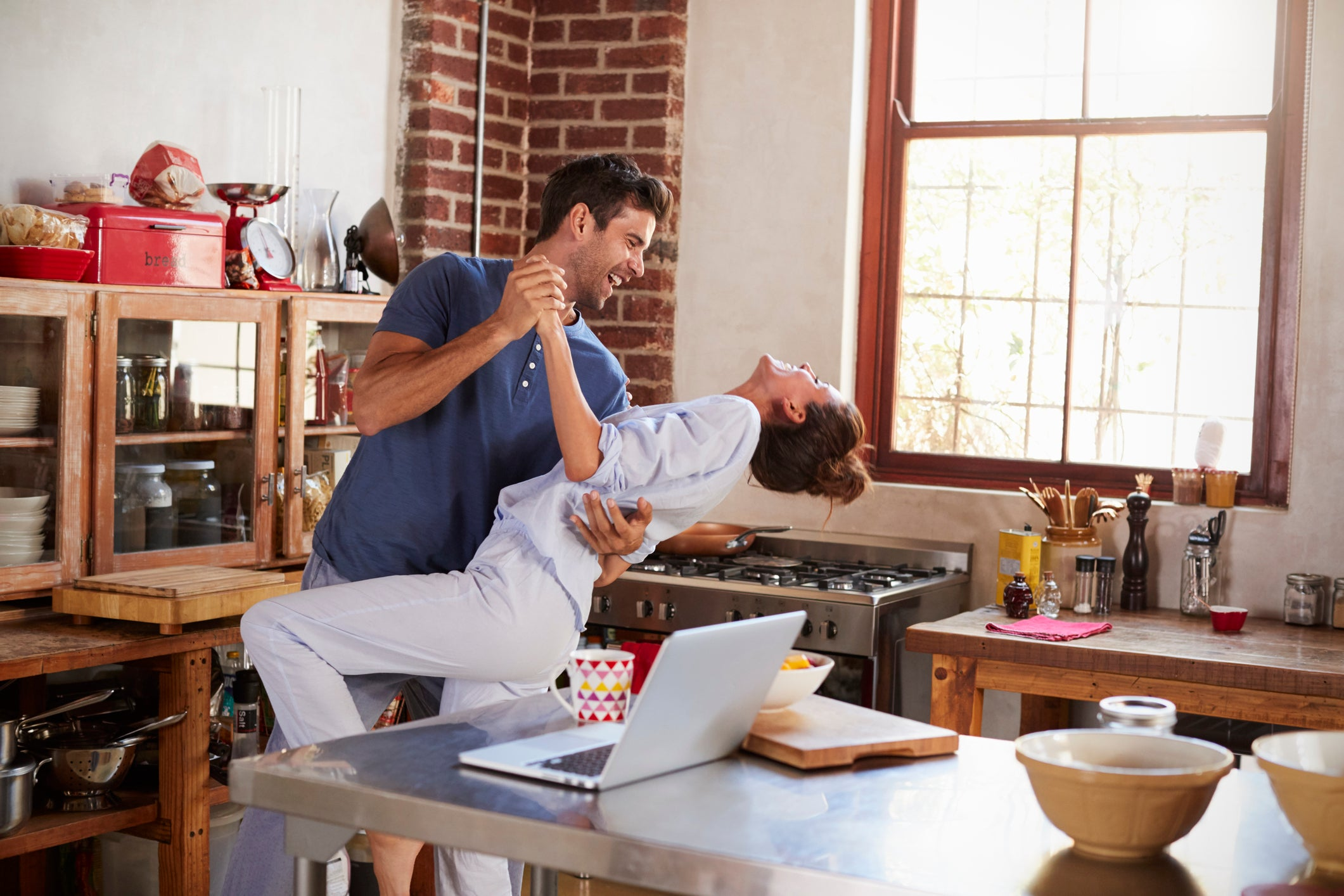 A happy couple dances in kitchen