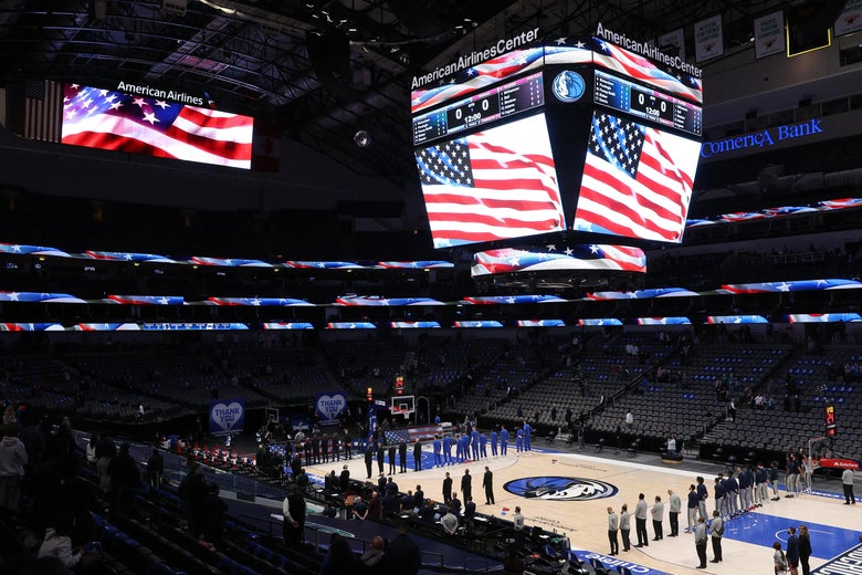 The Mavs and Pels stand for the anthem as the American flag is shown on the Jumbotron above the mostly empty arena