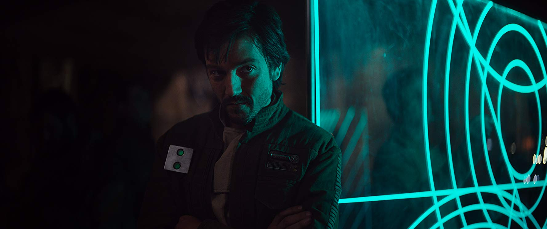 Diego Luna stands in the green light of a nearby monitor.