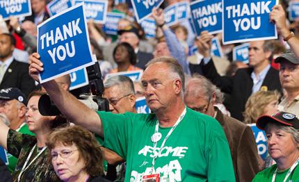 A delegate holds a thank you sign on the final day of the Democratic National Convention.