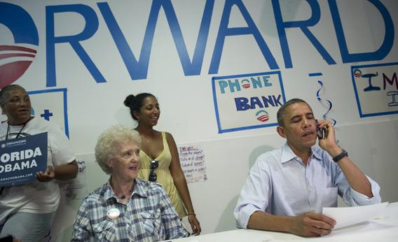 Obama makes a phone call to a supporter during a visit to the Obama for American campaign field office