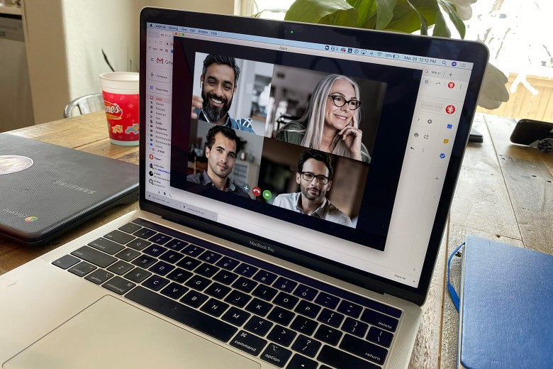 A laptop screen shows a Zoom call with four people on it.