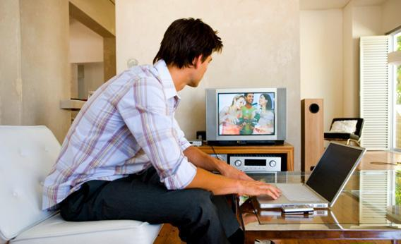 Man watching television with laptop.