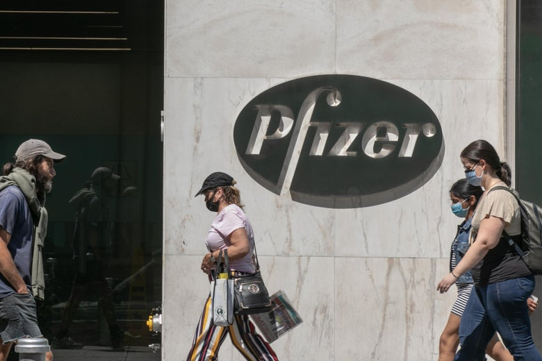 Pedestrians wearing protective masks walk past Pfizer Inc. headquarters in New York City.