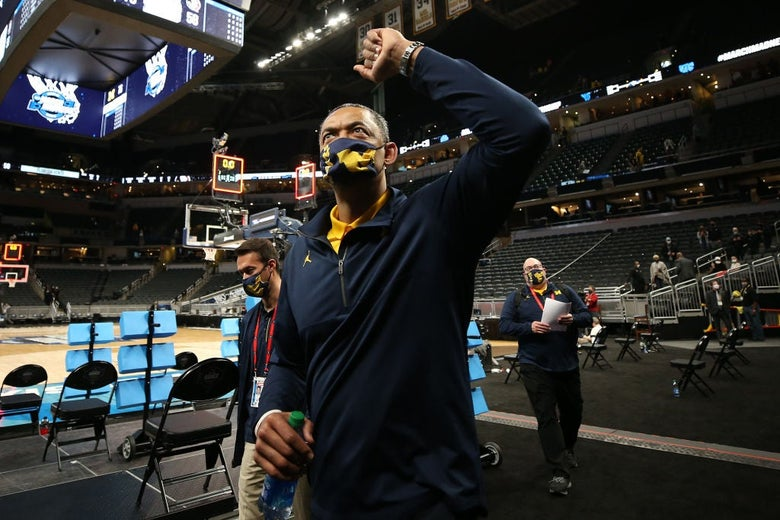Howard, wearing a mask and warmup gear, raises his fist as he looks toward the stands above him.