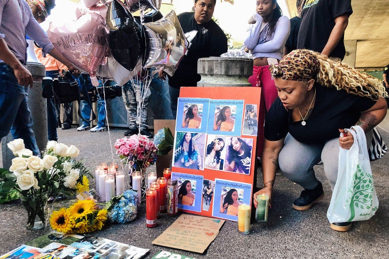 Malika Harris places a candle down for her sister Nia Wilson at a makeshift memorial.