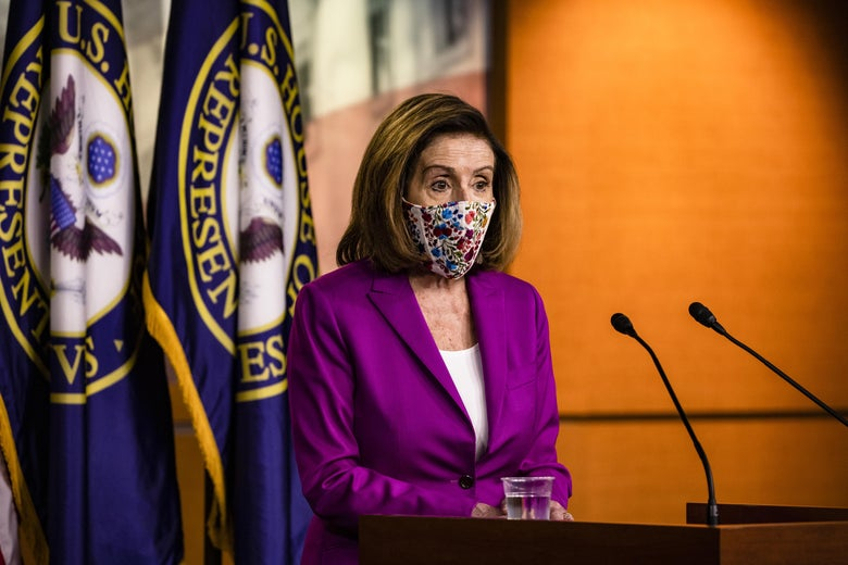 Pelosi speaks into two microphones while standing in front of two House of Representatives flags.