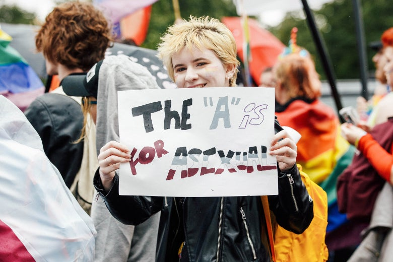 "A marcher in a black leather jacket holds a sign that says, ""The 'A' is for asexual."""