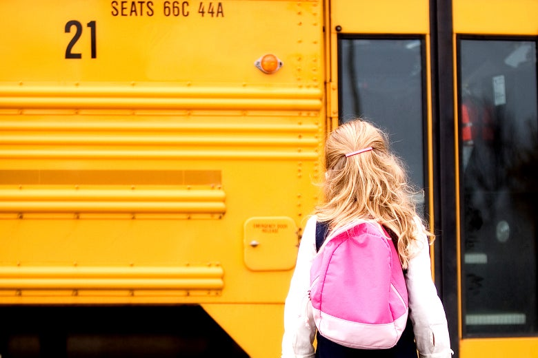 A girl walking to a school bus