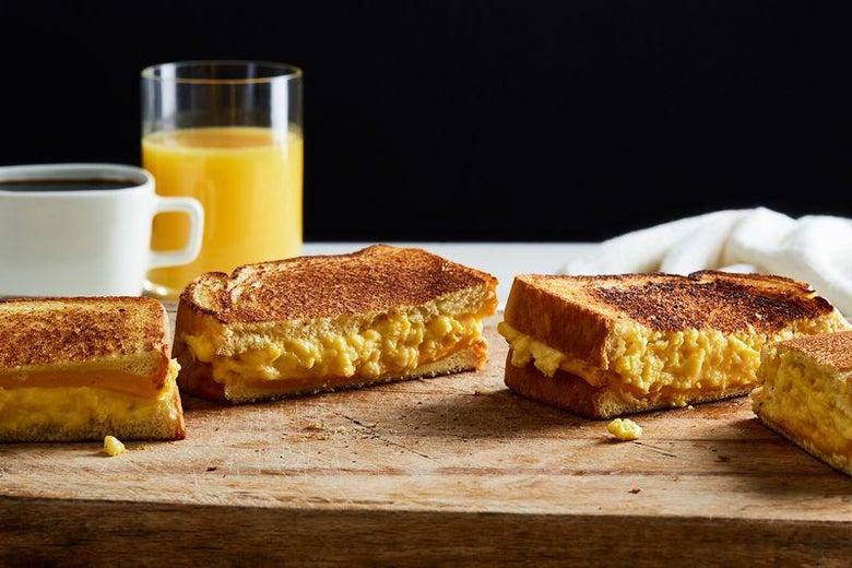 Cheesy breakfast sandwiches with orange juice.