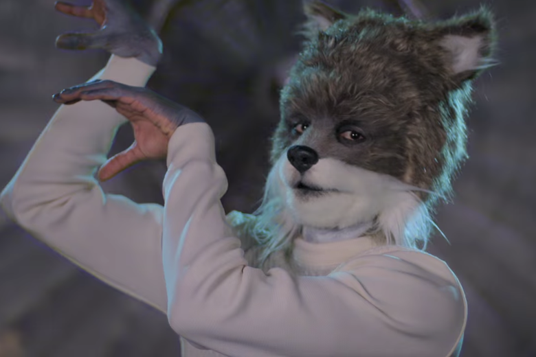 A man in white sweater with his hands up and wearing a wolf head.