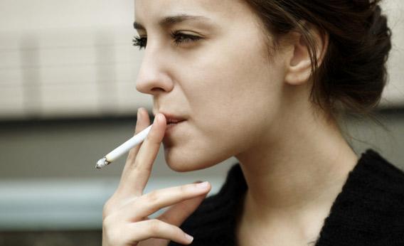 Woman smoking on a sidewalk.