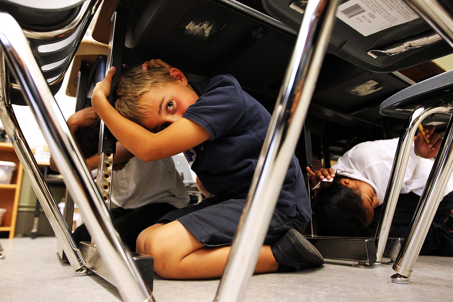 Students crouch under their desks covering their heads.