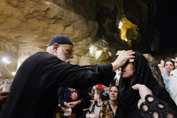 Coptic priest Father Samaan Ibrahim puts a cross on the forhead of an Egyptian woman.