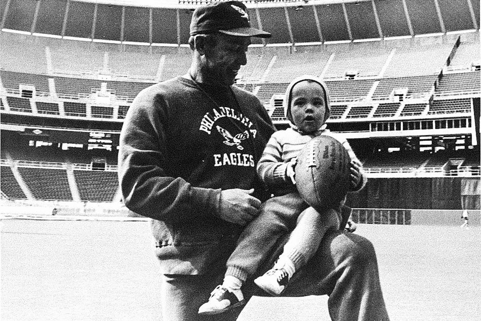 A black-and-white photo of the author as a toddler, holding a football, on the knee of his father inside a football stadium.