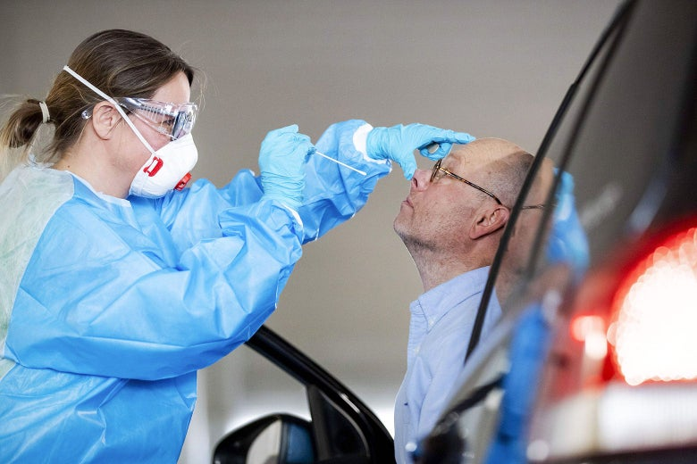 A medical worker wearing protective gear pushes up a patient's nose with one hand and lowers a long swab toward the nose with the other hand