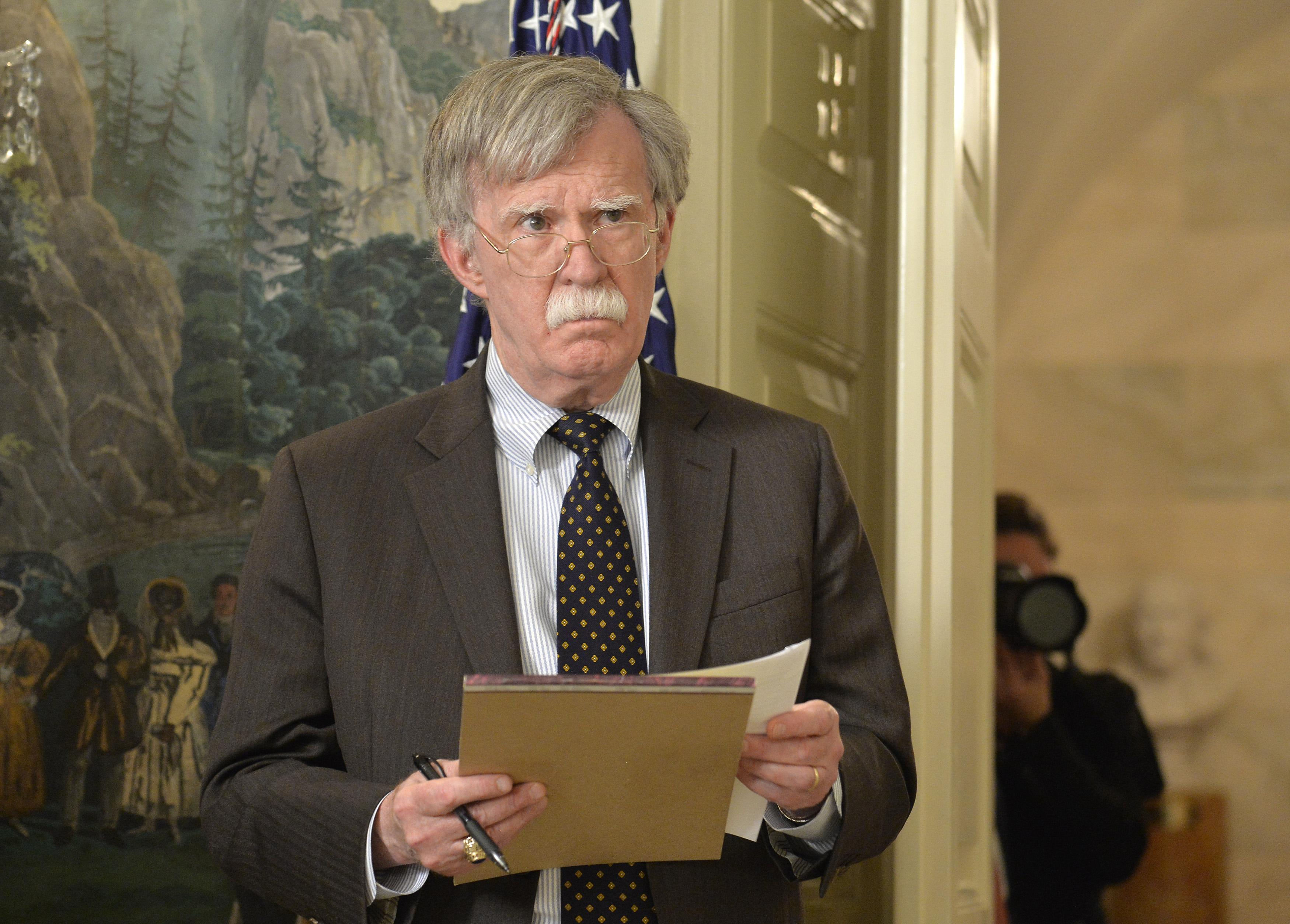 John Bolton holds a legal pad and pen.