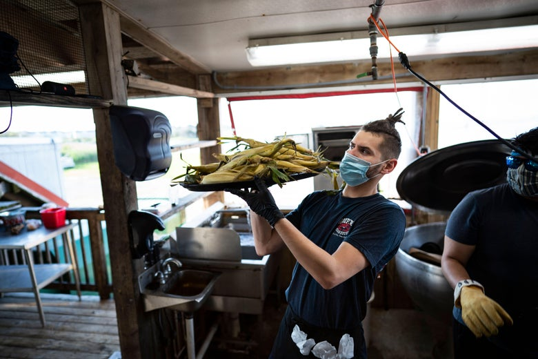 A server wears a mask and gloves while working, as Hoopers Crab House opens for in-person dining, amid the coronavirus pandemic, on May 30, 2020 in Ocean City, Maryland. - On the evening of May 29, 2020 restaurants and bars in the state of Maryland were opened for outdoor and open air dining. (Photo by Alex Edelman / AFP) (Photo by ALEX EDELMAN/AFP via Getty Images)