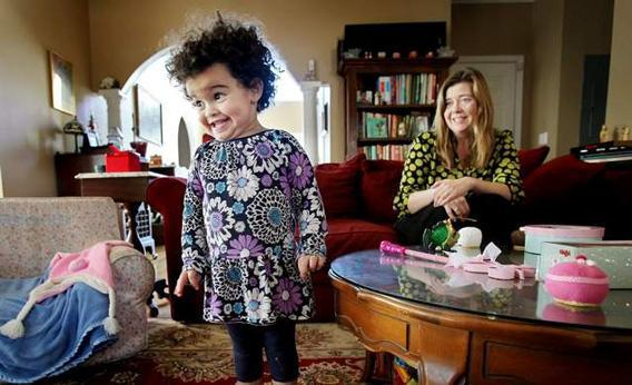 Melanie Capobianco smiles at Veronica as she plays with her Christmas toys.