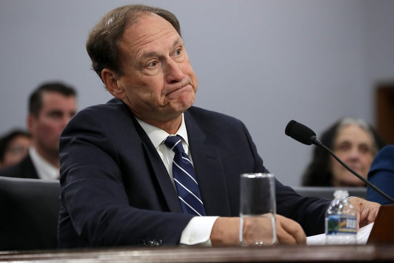 Justice Samuel Alito purses his lips while seated in front of a mic