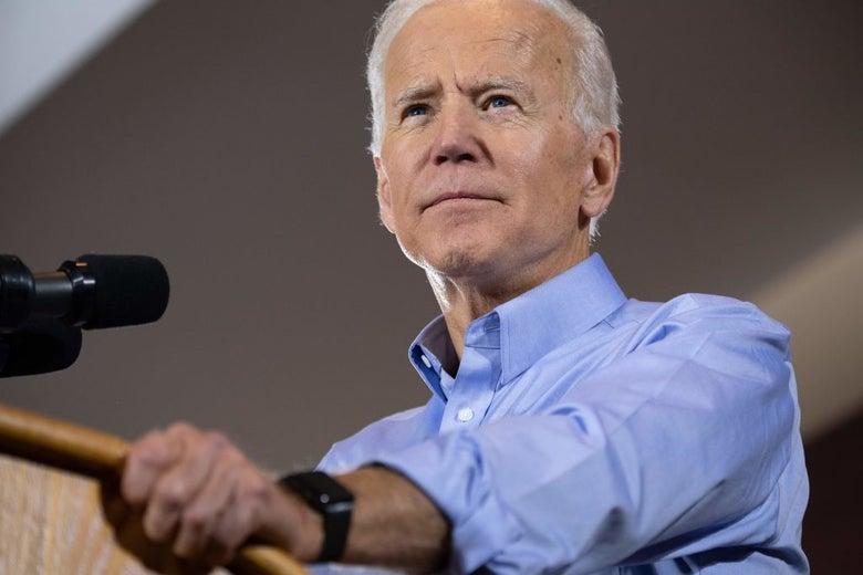 Biden, wearing a rolled-up blue shirt, grips a lectern.