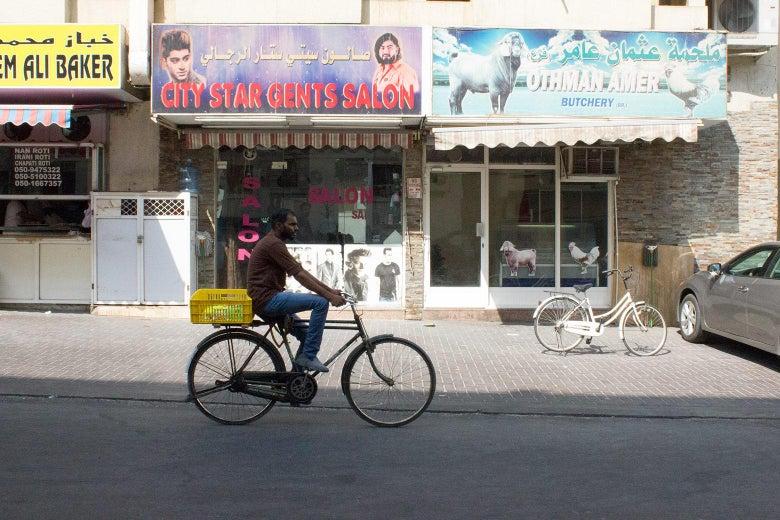 A man rides a bicycle past storefronts in Al Hamriya.