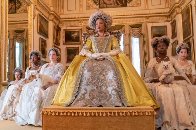 Golda Rosheuvel sits on an elevated platform wearing an opulent yellow gown and curly white wig, surrounded by ladies in waiting holding fluffy dogs.