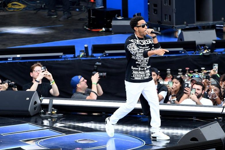 Ludacris holds a mic onstage as fans below him film with their phones