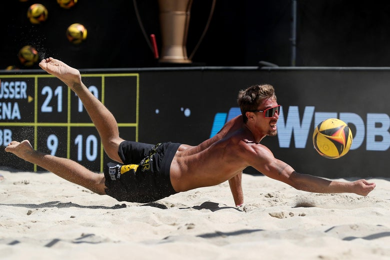 Crabb, wearing only shorts and sunglasses, dives toward the sand with his right arm outstretched to hit a yellow volleyball.