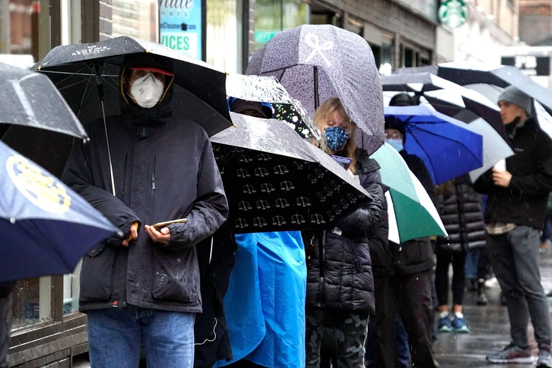 A line of people standing in the rain with umbrellas waiting to vote on the Upper East Side