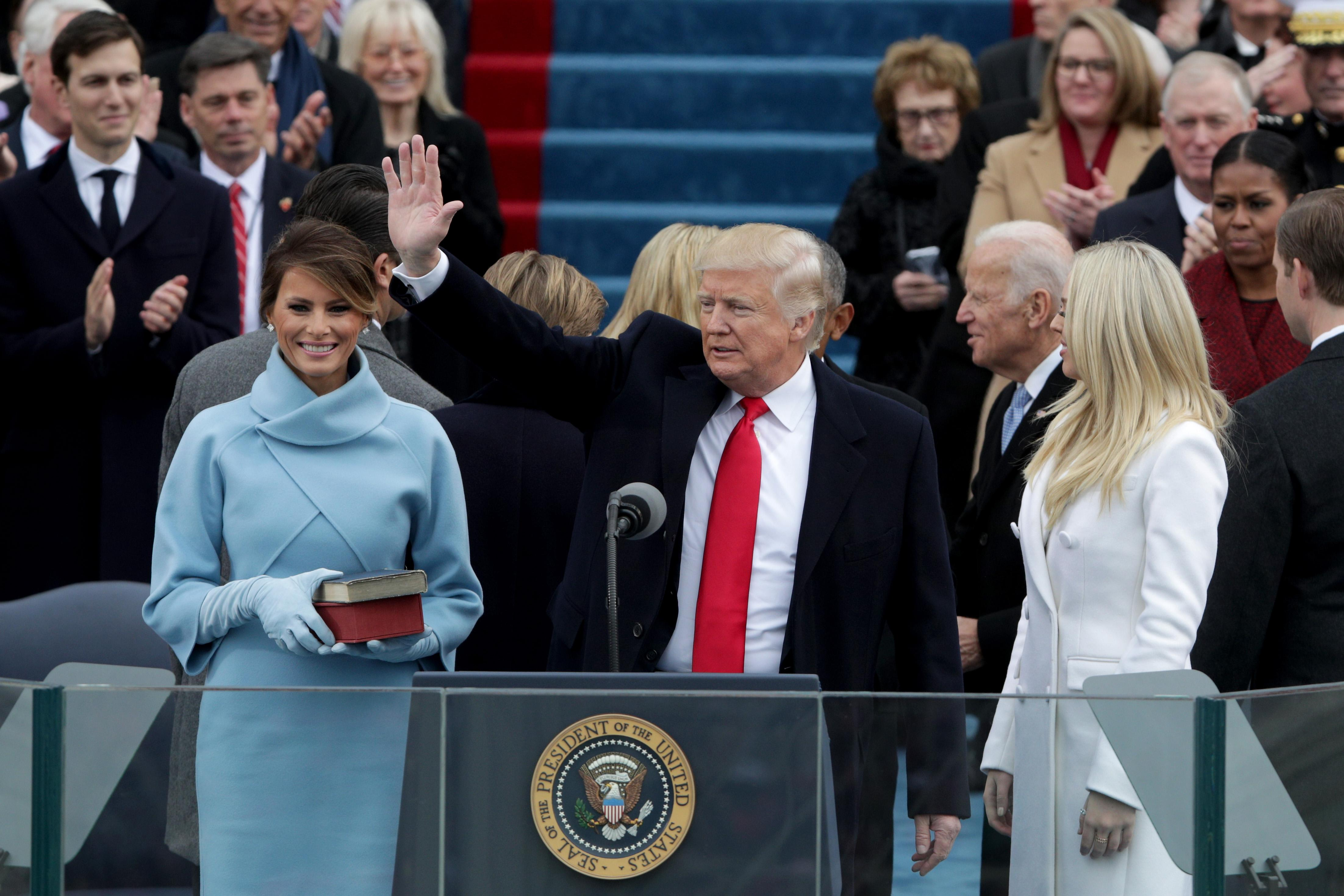Trump waves at his inauguration. Melania stands next to him, holding books. On the other side, his daughter Tiffany looks around.