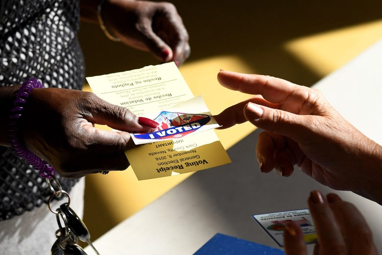 """A poll worker hands out an """"I Voted"""" sticker with the Las Vegas Strip on it."""