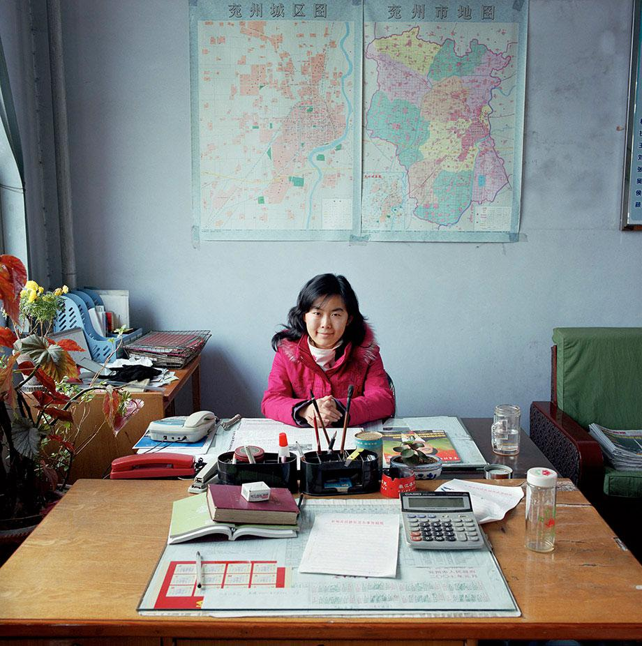 China, bureaucracy, (c) Jan Banning, 2007.Wang Ning (b. 1983) works in the Economic Affairs office in Gu Lou community, Yanzhou city, Shandong province. She provides economic assistance to enterprises in her region and is the liaison officer between the government and local enterprises: she helps them get a permit for land use, personnel insurances, environmental permits and taxation registration.There was (at the time) no heating in the room. The maps show regional industrial zones. Wang Ning is not married. She lives at home with her parents. She works from 8.30 to 12 am and from 14 to 16 am. She has no official paid holidays, except the national bank holidays and the weekends. Monthly salary: 2,100 renminbi ($ 260, euro 228).Wang Ning (1983) is adviseur op het Bureau voor Economische Zaken van Gu Lou, een wijk in de stad Yanzhou die valt onder de prefectuur Jining, provincie Shandong. Ze is een soort verbindingsofficier tussen de overheid en lokale ondernemingen: ze helpt hen aan vergunningen, aan info over de eisen w.b. administratie en werknemersrechten. Wang Ning is ongehuwd, ze woont bij haar ouders. Ze werkt vijf dagen per week van half negen tot twaalf en van twee tot vier uur. Ze heeft in oktober een week vakantie en drie dagen met Chinees Nieuwjaar. Maandsalaris: 2100 renminbi (€ 228, euro 228).