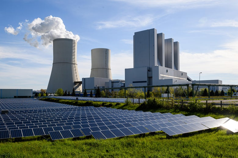 A solar energy field is seen next to a smoking coal plant.