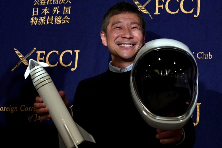 Yusaku Maezawa holds a model rocket in one hand and a space helmet in the other at a SpaceX event. He is smiling broadly and wearing a collared shirt under a sweater.