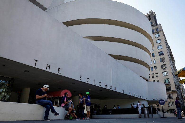 People sit outside The Guggenheim Museum in New York City on August 30, 2017.