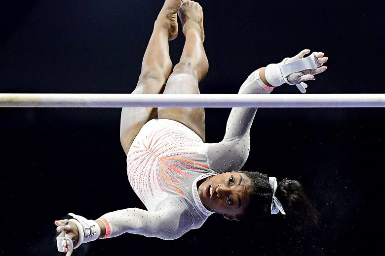 Simone Biles flipping upside-down during her uneven bars routine