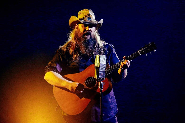 Chris Stapleton holding a guitar and singing into a microphone.