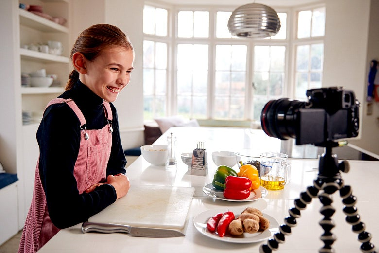 A young girl standing in a kitchen grins at a camera set up on the counter.