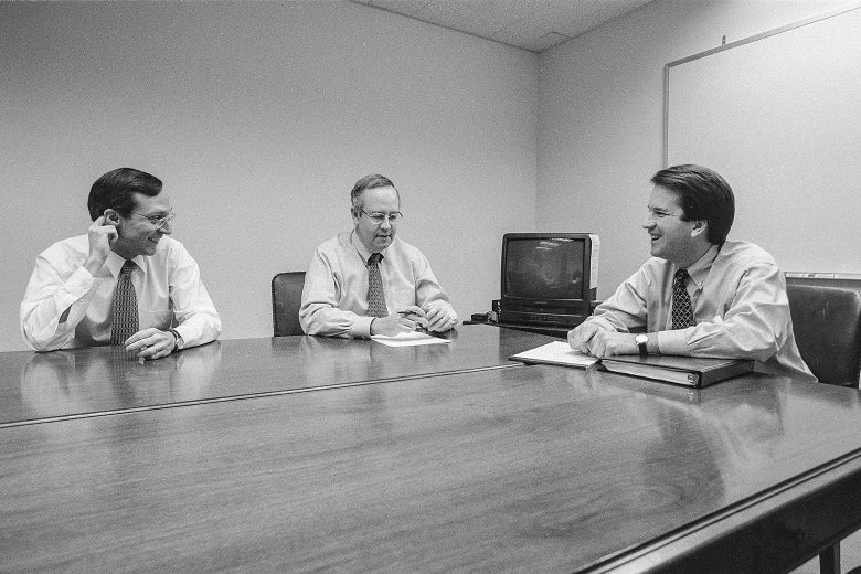 Black and white photo of Starr, Bates, and Kavanaugh sitting at a conference table in a drab room. Bates and Kavanaugh smile broadly.