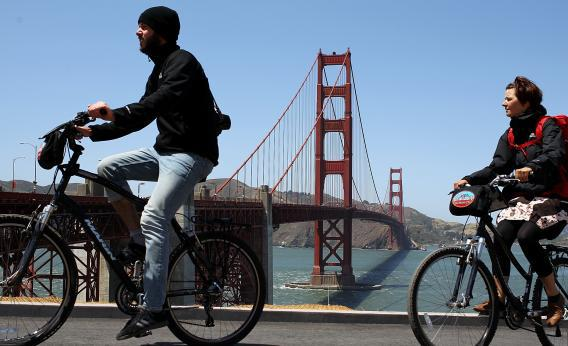 Tourists ride bicycles past the Golden Gate Bridge.