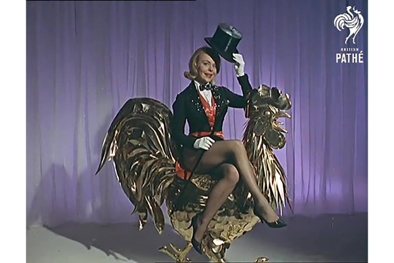 A woman in a showgirl outfit tips her hat while sitting sidesaddle atop a giant golden statue of a rooster.