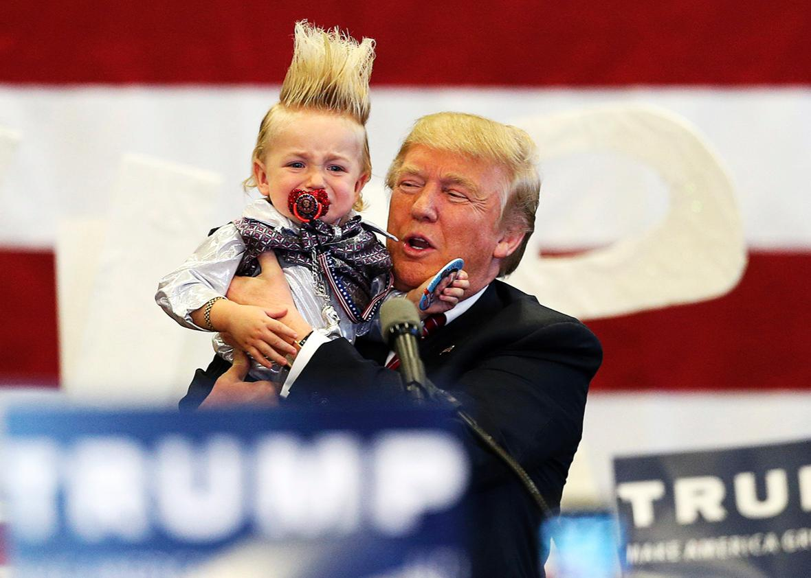 Republican U.S. presidential candidate Donald Trump holds up a crying young child from the crowd as he arrives at a Trump campaign rally in New Orleans, Louisiana March 4, 2016.