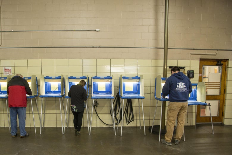 Three people vote at booths.