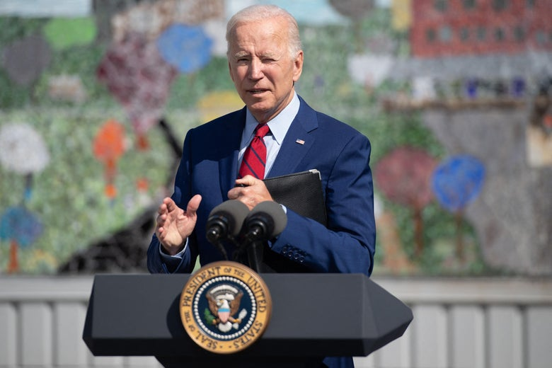 Joe Biden stands outside behind a presidential podium with a mural behind him.