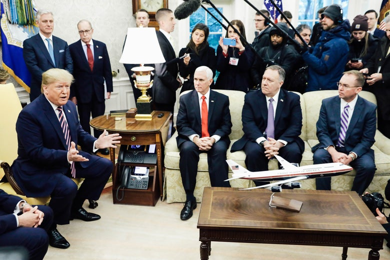 On the left, Donald Trump sits on a chair and speaks, with Robert O'Brien and Larry Kudlow standing behind. Mike Pence, Mike Pompeo, and Mick Mulvaney sit on a couch near Trump and look at him as reporters hold up microphones behind them.