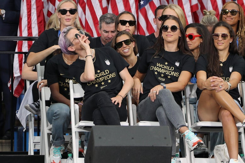 Megan Rapinoe pretends to sip tea, seated next to Alex Morgan on a stage, with several other USWNT players around them. They are all wearing sunglasses.