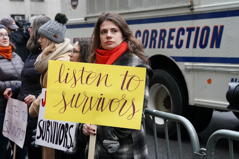 """A woman holds a sign that says """"listen to survivors"""" standing outside the courthouse on the first day of Harvey Weinstein's trial."""