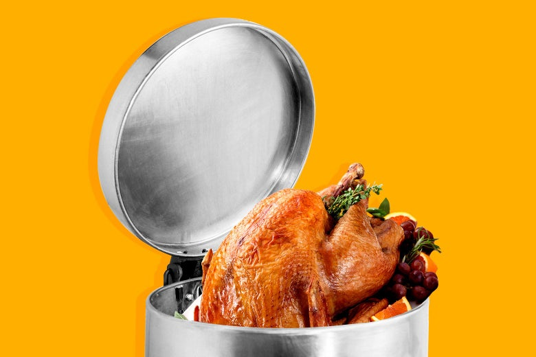 A glistening roasted Thanksgiving turkey sticking out of a trash can