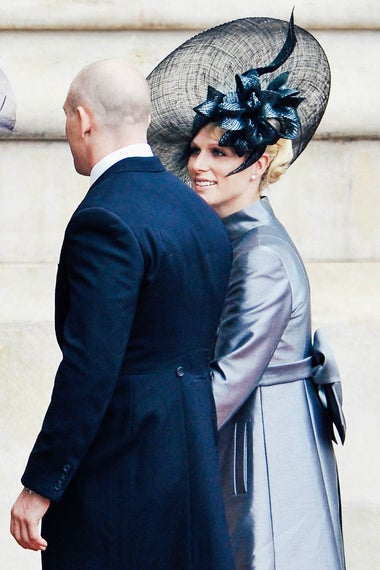 Zara Phillips wears a silver dress and elaborate black-silver hat.